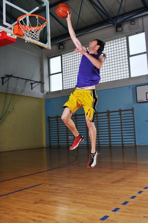 one healthy young  man play basketball game in school gym indoor Stock Photo - 5272665