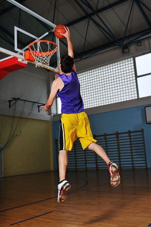 one healthy young  man play basketball game in school gym indoor Stock Photo - 5272724