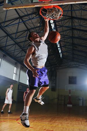 high school basketball: one healthy young  man play basketball game in school gym indoor