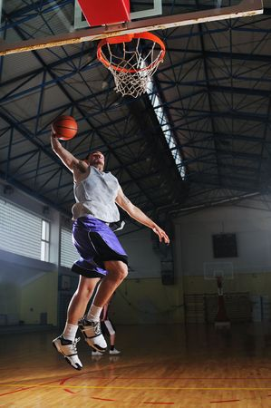 basketball player: one healthy young  man play basketball game in school gym indoor