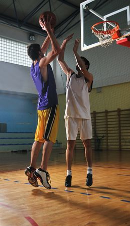 competition cencept with people who playing basketball in school gym photo