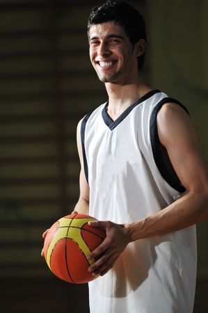 high school basketball: one basket ball game player standing in sport gym with ball Stock Photo