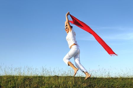 beautiful young and healthy woman run and jump on meadow at sunny day with red scarf Stock Photo - 5285230