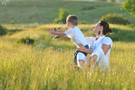happy child and woman outdoor playing with soap bubble on meadow Stock Photo - 5293515