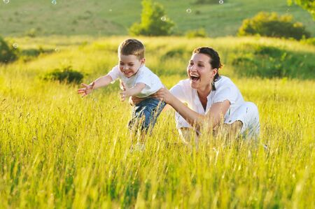 happy child and woman outdoor playing with soap bubble on meadow photo