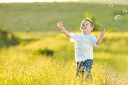 pompas de jabon: feliz ni�o hermoso joven divertirse en eadow juguete con burbujas de jab�n