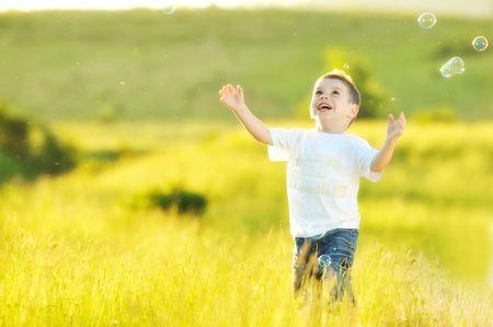 blow: bel bambino felice giovani si divertono a eadow con bolle di sapone giocattolo Archivio Fotografico