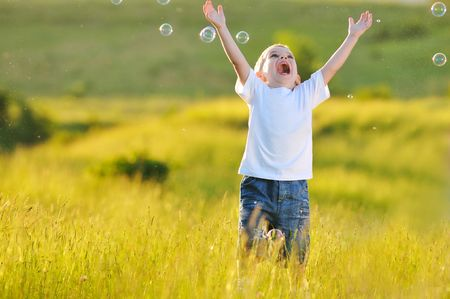blowing wind: happy young beautiful child have fun on eadow with soap bubbles toy