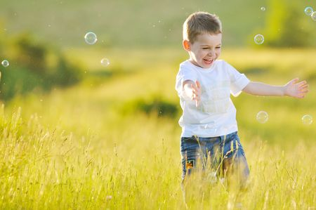 happy young beautiful child have fun on eadow with soap bubbles toy Stock Photo - 5321290