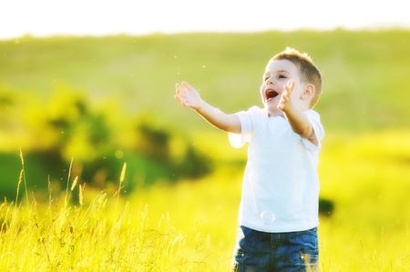 happy young beautiful child have fun on eadow with soap bubbles toy photo