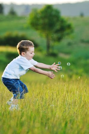 happy young beautiful child have fun on eadow with soap bubbles toy Stock Photo - 5325433