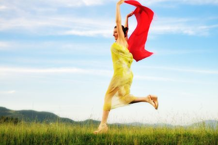 beautiful young and healthy woman run and jump on meadow at sunny day with red scarf photo