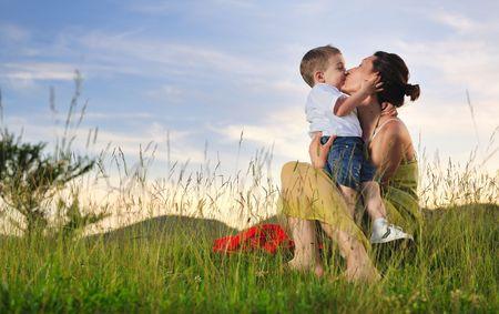 Gelukkig jonge vrouw moeder spelen en buiten met mooie kind