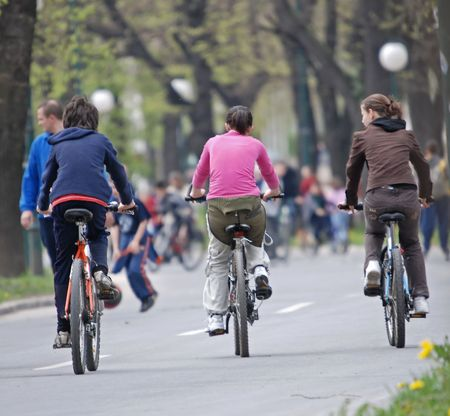 road cycling: three teens riding bike in park Stock Photo
