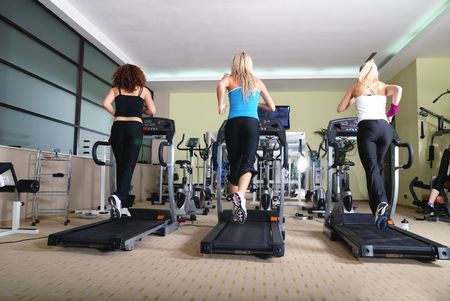 three healthy girls running on threadmill in fitness club