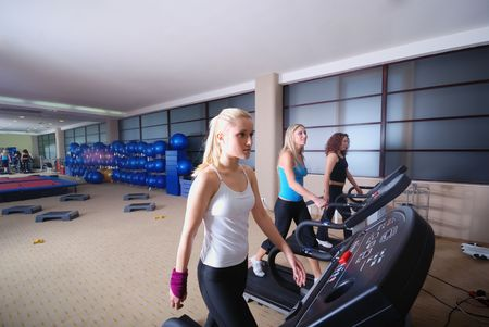 group of girls working out on treadmill at  fitness gym photo