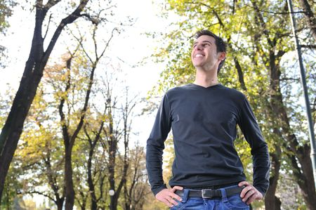 eyecontact: Handsome young man smiling outdoors in nature Stock Photo
