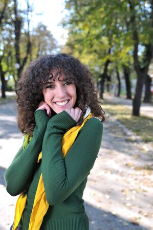 eyecontact: brunette Cute young woman with colorful scarf smiling outdoors in nature   Stock Photo
