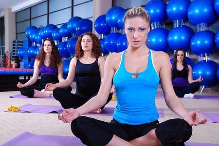 beautiful girls meditating in fitness club photo