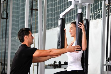 woman in the fitness gim working out with personal trainer coach photo
