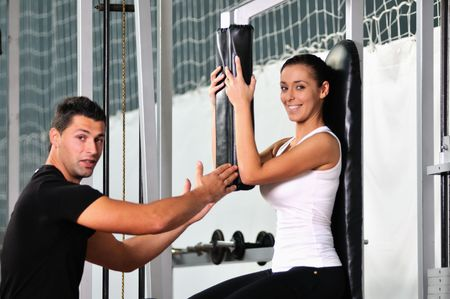 athletics training: woman in the fitness gim working out with personal trainer coach