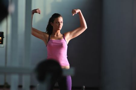 young woman with strong arms rising hands in air and representing their streinght and vitality photo