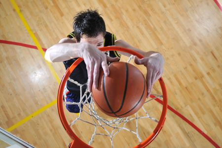 basketball shot: one healthy young  man play basketball game in school gym indoor