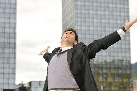 cielos abiertos: Retrato del joven empresario al aire libre y feliz