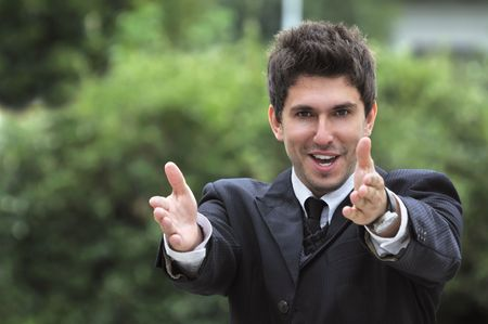 Young caucasian business man in a suite, pointing at camera to you photo