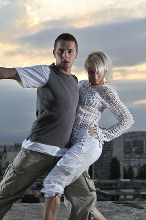 romantic urban couple dancing on top of the bulding photo