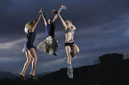 group of people jumping in air in night photo