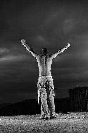 arms wide open: Man with his arms wide open outdoor against dark sky