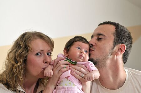 indoor portrait with happy young family and  cute little baby photo