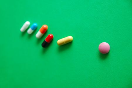 deleterious: pills on green background Stock Photo
