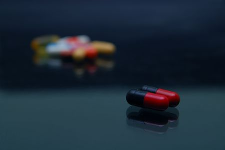 deleterious: pills on glossy surface with reflection Stock Photo
