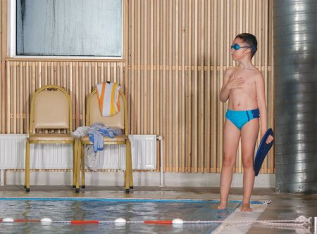 little boy swimming: child group  at indoor pool on swimming school training