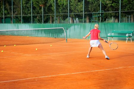 Girl playing tennis outdoor on court photo