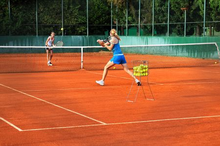 tennis court: Two young women playing tennis outdoors on court Stock Photo
