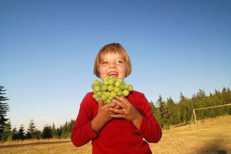 happy girl with grape outside photo