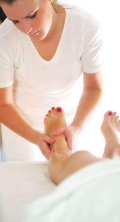 beautiful woman having leg and foot massage at the spa and wellness center photo