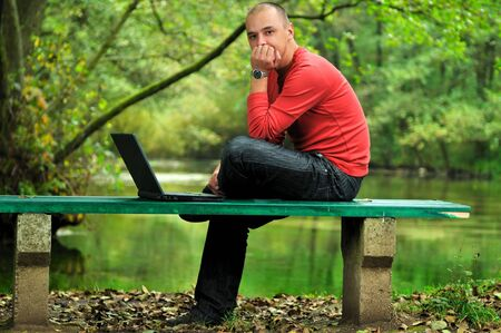 one young businessman working on laptop outdoor with green nature in background Stock Photo