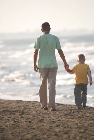 father and son walking on beach photo