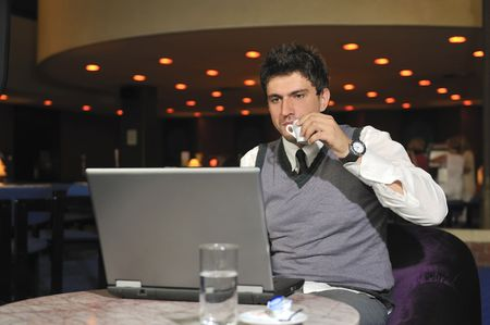 buisinessman: Young buisinessman drinking coffe while working on laptop
