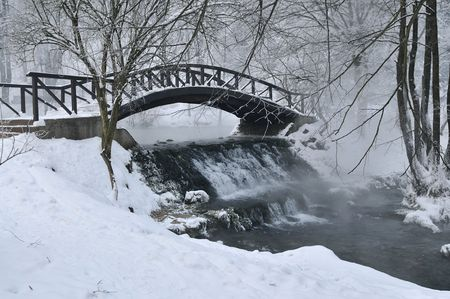 frozen creek: small wooden bridge over cold river at early mornig at winter season
