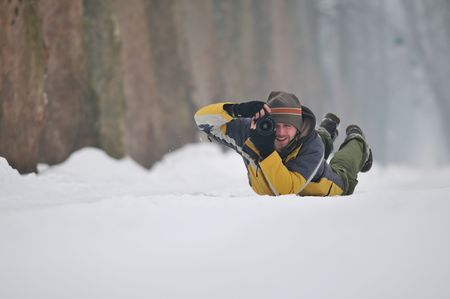 pro photographer with yellow jacket lie on snow and making shoot photo
