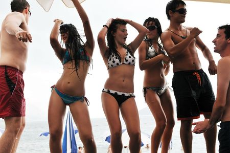 rave: young happy people have fun and dancing on beach at sumer time with rain