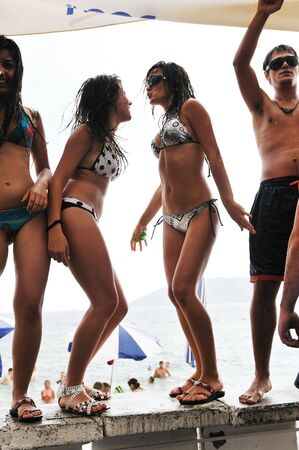 drunk girl: young happy people have fun and dancing on beach at sumer time with rain