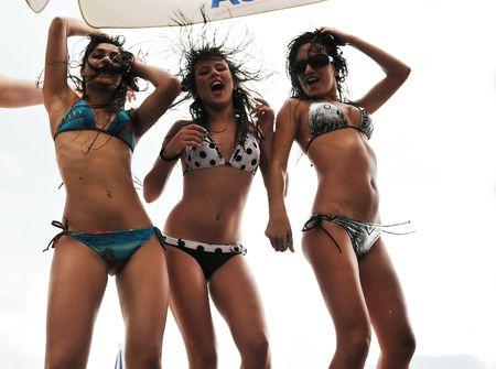 ni�as en bikini: feliz a la gente joven divertirse y bailar en la playa en el momento de consumidor con la lluvia