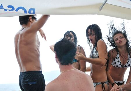 young happy people have fun and dancing on beach at sumer time with rain photo
