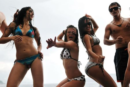 drunk party: young happy people have fun and dancing on beach at sumer time with rain